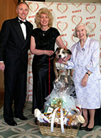 Foxy accepts his award from the Hartz Mountain Corporation along with his owner Mrs. Maquire.